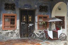 Trishaw med gammal tegelstenhusbyggnad i George Town världsarv arkivbilder