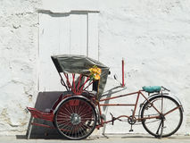 Trishaw parked at a white wall. Red, Asian trishaw parked in front of a white concrete wall in Georgetown, Penang, Malaysia Royalty Free Stock Images