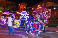 Trishaws coloridos adornados con las luces y las imágenes multicoloras brillantes de la historieta en Malaca Imagen de archivo