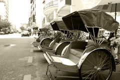 Trishaws (Monochrome). Black and white image of traditional trishaws parked at the roadside stock image