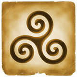 Triskelion spiral symbol old paper. Triskelion mark on weathered papyrus. Three interlocked spirals sign. Mysterious magical symbol. Ancient Celtic culture Royalty Free Stock Photography