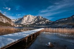 Trisselwand and Lake Altaussee with a wooden runway. Runway in Altaussee with the wonderdul lake and the mountains in the background Royalty Free Stock Photography