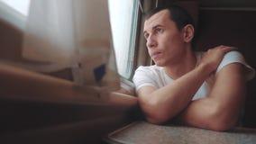 Triste do homem furado montando uma estrada de ferro do trem olha para fora a janela curso da viagem da estrada de ferro do trem  video estoque