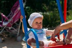 Triste, menina em um vestido branco e chapéu, montando em um balanço, em um sol do verão e em um calor playground infância, seren foto de stock