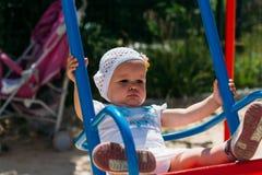 Triste, menina em um vestido branco e chapéu, montando em um balanço, em um sol do verão e em um calor playground infância, seren imagem de stock