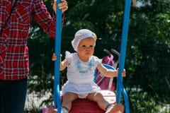 Triste, menina em um vestido branco e chapéu, montando em um balanço, em um sol do verão e em um calor playground infância, seren fotografia de stock