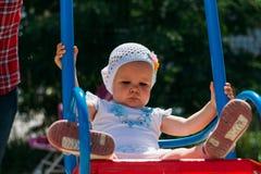 Triste, menina em um vestido branco e chapéu, montando em um balanço, em um sol do verão e em um calor playground infância, seren foto de stock royalty free