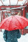 Triste y solamente mujer que caminan en nieve a través del ambiente urbano fotografía de archivo