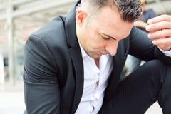 Tristesse se reposante d'homme d'affaires et travail de pensée sur la rue de marche image stock