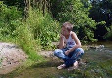 Tristeza adolescente da costa da areia da água da reflexão da manhã do bosque do verão da água do rio do menino Fotos de Stock Royalty Free
