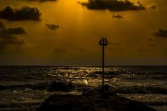 Trisulam sur une roche parmi les vagues de plage image libre de droits
