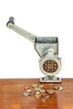 Tritacarne con le monete sulla tavola di legno e sul fondo bianco Fotografia Stock