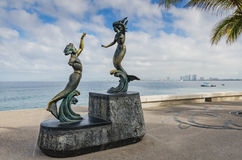 Triton and Mermaid - Puerto Vallarta, Mexico. Bronze sculpture by Carlos Espino focusing on beauty of human form on artwalk along Malecon, waterfront esplanade Royalty Free Stock Photo