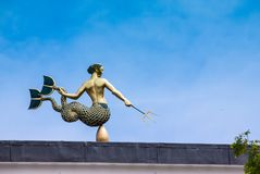 Triton weather vane in London. Tritorn weather vane on the top of building in London with blue sky stock photos