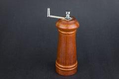 Triturador de madeira da pimenta no fundo preto Fotos de Stock
