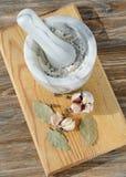 Triturador, pimienta inglesa, ajo y hoja de laurel en un fondo de madera Imagen de archivo libre de regalías