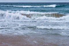 Trituradores que acometen sobre la orilla con el espray y la espuma en un día tempestuoso en la playa imagen de archivo