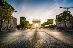 Triumf- båge på slutet av den Champs-Elysees gatan för solnedgång Royaltyfri Bild