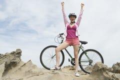 Triumferande kvinna på bergstoppet med mountainbiket Royaltyfri Fotografi