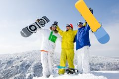 Triumph. Portrait of three successful snowboarders raising their arms on mountain top Royalty Free Stock Images