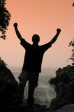 Triumph. Silhouette of man at viewpoint with arms raised Stock Image