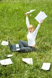 Triumph. Portrait of joyful female sitting on green grass with raised arms during her work Royalty Free Stock Photos