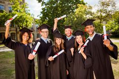 Triumph, education, graduation and people concept - group of hap stock image