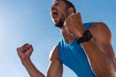 Triumph. Excited sportsman with smart watch celebrating triumph and yelling, with blue sky on foreground Royalty Free Stock Photography