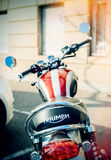 Triumph Motorcycles parked in city street sun flare Stock Images