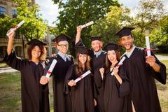 Triumph, onderwijs, graduatie en mensenconcept - groep hap stock afbeelding