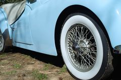 Triumph sports car closeup with white wall tire. This sleek classic 1950s pale blue Triumph convertible auto has extra wide white wall tires. Wide white wall Stock Image