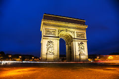 The Triumphal Arch Arc de Triomphe in Paris, France. At night Stock Photos