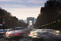 Triumphal Arch and Champ Elysses with moving cars in Paris Stock Photo