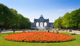 Triumphal Arch in Cinquantenaire Parc. BRUSSELS BELGIUM - April 13, 2014: Triumphal Arch Arc de Triomphe in the Cinquantenaire park in Brussels with flowers Stock Photos