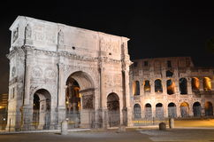 Triumphal Arch of Constantine nearby Colosseum in Rome against blue sky, Italy Stock Images
