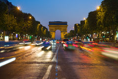 The Triumphal Arch in Elysian Fields. PARIS, FRANCE - JULY 9: Elysian Fields Avenue on July 9, 2013 in Paris. It ends at the Triumphal Arch, built to honour the stock photography