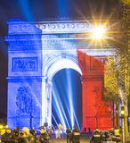 The Triumphal Arch lit up with the colors of French national  fl. Paris, France-January 01, 2016: The Triumphal Arch(focus) lit up with the colors of French Stock Photo