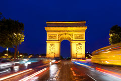 Triumphal Arch in Paris, France. Evening traffic on Champs-Elysees in front of Arc de Triomphe (Paris, France Royalty Free Stock Photography