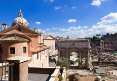 A triumphal arch and Roman Forum, Italy.Cityscape in a sunny day Stock Photos