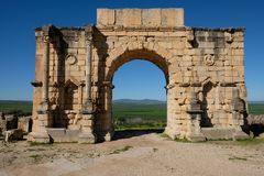 Roman Ruins gate in volubilis in morocoo. The Triumphal Arch at Volubilis in Morocco. The impressive ruins of this regional Roman capital sit surrounded by a mix Stock Image