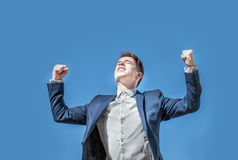 Triumphant business man rising his arms over blue sky background Royalty Free Stock Image