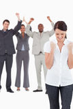 Triumphant businesswoman with cheering colleagues behind her Stock Image