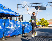 Triumphant Leap. Older woman in great physical condition leaps in triumph and jubilation as she completes her very first 5k run at the 2016 Montgomery, Alabama stock image