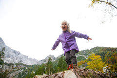 Triumphant little girl celebrating after climbing a rock Stock Photo