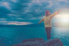 Triumphant little girl on lake shore royalty free stock photography