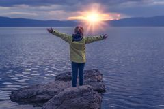 Triumphant little girl on lake shore stock images