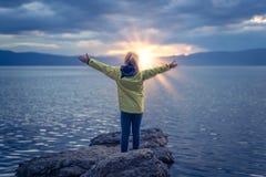 Triumphant little girl on lake shore stock photo