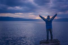 Triumphant man on lake shore. Triumphant man lifting his hands high in the air while standing on the large boulders on the shore of Lake Ohrid, Republic of stock photography