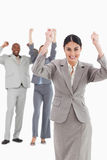 Triumphant saleswoman with cheering associates behind her Royalty Free Stock Image