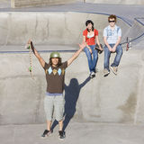 Triumphant skateboarder. Gestures infront of his friends Stock Image